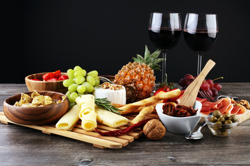 Tapas or Italian antipasti wine snacks set. Cheese variety, Mediterranean olives, pickles, Prosciutto di Parma with grapes, wine in glasses over black grunge background