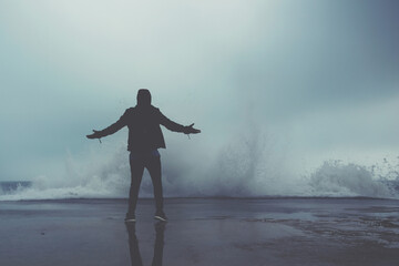 Rear view of a adult man standing with arms raised in front of the sea despite a great wave hits the shore, young male enjoying breathtaking scenery of the sea at cool overcast rainy day