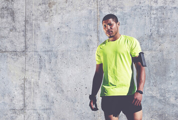 Tired sportsman with armband on the arm resting after an workout while standing against cement wall background with copy space area for text message or advertising, man runner taking break after run