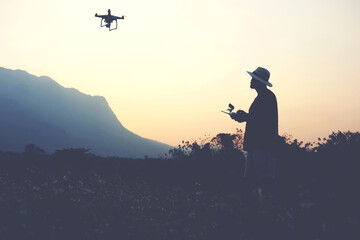 Silhouette of a man photographer is taking photo on flying quadcopter with camera, while is standing against sunset and alp. Young male traveler is using RC multicopter during summer trip overseas