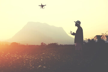 Silhouette of a man photographer is making picture with RC aerial drone, while is standing in rural in evening. Male traveler is shooting video with flying multicopter during summer adventure abroad