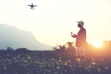 Silhouette of a man photographer is using RC aerial drone for video shooting, while is standing in rural against beautiful sunset. Male tourist is taking photo on flying quadcopter during summer trip