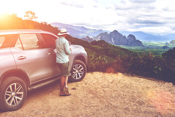 Young hipster man is looking away, while is standing near his rental automobile on a hill in Thailand. Male tourist is enjoying fantastic jungle view during long awaited summer trip on suv in Asia