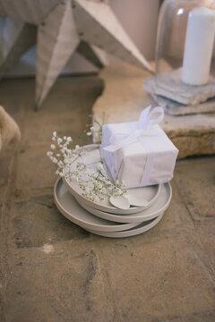 Assiettes blanches avec paquet cadeau et fleurs ambiance de Noel