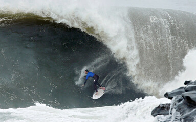 Faulks catches a wave during the Cape Fear surfing tournament in heavy seas off Sydney's Cape Solander in Australia