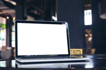 Mockup image of laptop with blank white screen on wooden table in coffee shop
