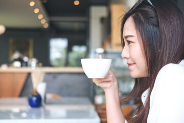 Closeup image of a beautiful Asian woman smelling and drinking hot coffee with feeling good in modern cafe
