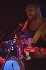 Male singer performing with guitar in night club