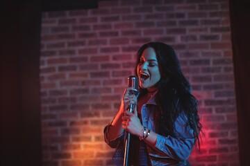 Cheerful singer singing illuminated nightclub