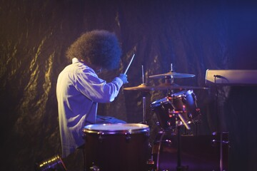 Male drummer with frizzy hair playing drum kit in nightclub