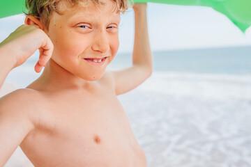 Boy portrait on the sea beach with swiming mattress