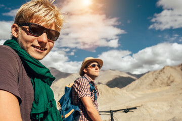 Two travelers on bycikles in high mountain