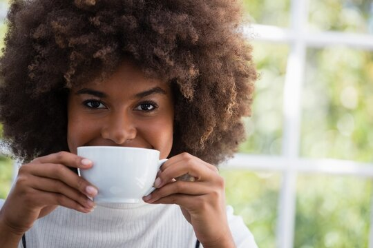 Close up portrait of smiling woman having coffee in cafe