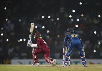 West Indies' Ramdin hits a boundary as lights from spectators' mobile phones are seen in the background during the second Twenty 20 International cricket match against Sri Lanka in Colombo
