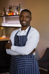 smiling waiter standing with arms crossed in restaurant