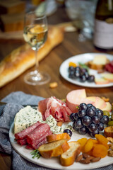 Wine and cheese platter on table with white wine.