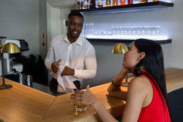 Bar tender talking with beautiful woman