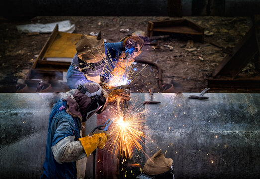 Welder is welding big pipe at construction site