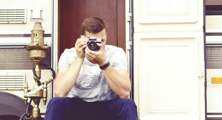 Young, handsome hipster taking pictures outdoors at summer. Holiday, journey, vacation concept.