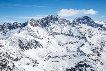 Aerial view of the Bernina Group in its winter version with the Sasso d'Entova and Pizzo Tremogge in the foreground and the Pizzo Bernina in the background, Valmalenco, Valtellina, Italy