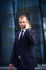 businessman talking on his cellphone while walking outdoors