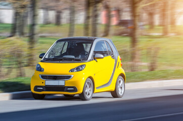 Miniature small city car of yellow color at speed in the city.