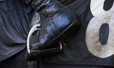 A close up of a mud covered jockeys boot as he returns after riding in the 13.30; The Trisoft Mares' Handicap Hurdle
