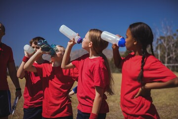 Trainer and kids drinking water in the boot camp