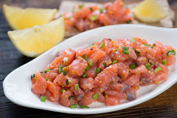 Close-up of salmon tartar served in a white plate, selective focus, shallow depth of field