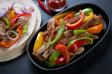 Cast-iron frying pan with mexican traditional fajitas, close-up, selective focus