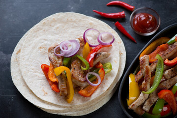 Wheat wraps filled with mexican pork fajitas, dark metal background, studio shot
