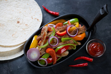 Frying pan with pork fajitas and tortillas on a dark metal background, elevated view, horizontal shot