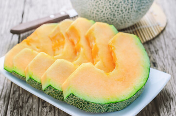 apanese melons at white dish on wooden table