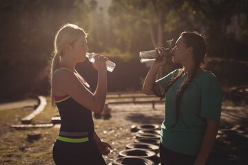 Friends drinking water after workout during obstacle course
