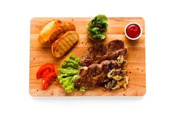Grilled steaks and vegetables on cutting board on white background