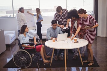 Handicap business people with colleagues in creative office