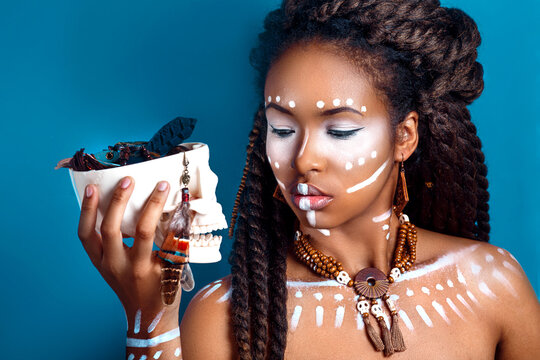 African style woman . Attractive young woman in ethnic jewelry . close up portrait of a woman with a painted face. Creative makeup and bright style.