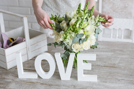 Making wedding bunch in floristry workshop. Unrecognizable florist assembling tender bouquet with white roses, fresh laurel and wild flowers. Decor or beautiful gift for lovely woman.