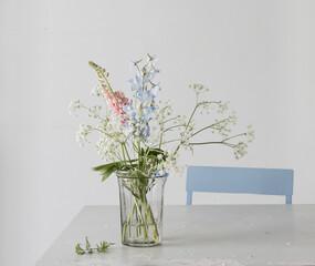 Wiesenblumen mit Kerbel und Lupinen in Glasvase auf Tisch