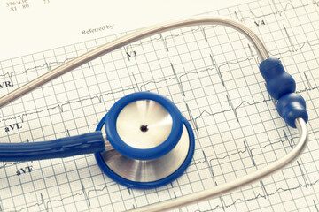 Stethoscope with ekg cardiograms chart. Filtered image: cross processed vintage effect.