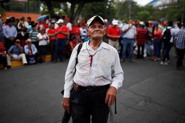 A supporter watches El Salvador's President Salvador Sanchez Ceren's third State of the Nation address during a rally outside the Salvadoran congress in San Salvador, El Salvador