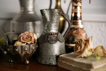 Antique pot with silver coins surrounded with other old objects and dried flowers; selective focus background.