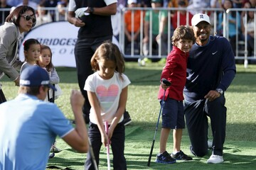U.S. golfer Woods poses for a photo with a child during a golf clinic in Mexico City
