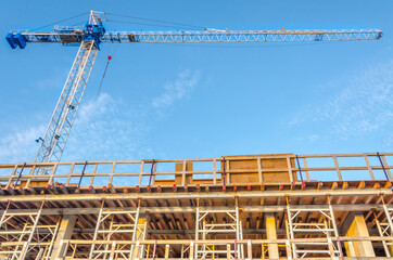 High-rise building under construction. The site with crane against blue sky with white clouds.