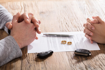 Couple's Hand On Divorce Agreement Wit Car Keys