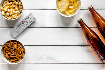 cinema and TV whatching with beer, crumbs, chips and pop corn white wooden background top view mock-up