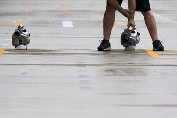 A Red Bull Formula One pit crew member dries rain water from pit lane ahead of the first practice session of the U.S. F1 Grand Prix at the Circuit of The Americas in Austin