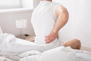 Man Sitting On Bed Having Back Pain