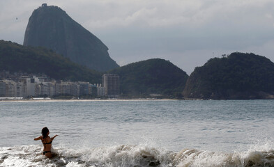 Woman is pictured with the Sugar Loaf mountain in background on Copacabana beach in Rio de Janeiro