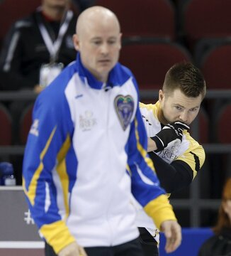 Team Manitoba skip McEwen peers around Team Alberta skip Koe as he lines up a shot during their page playoff game at the Brier curling championships in Ottawa